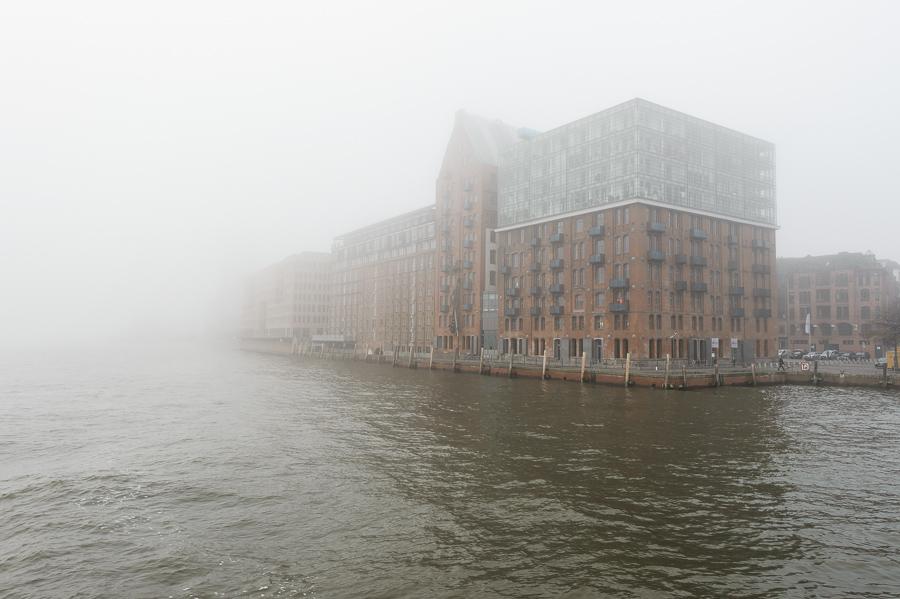 Der Kaispeicher in Altona, Hamburg versinkt im Nebel. Aufgenommen von der HADAG Elbfähre.